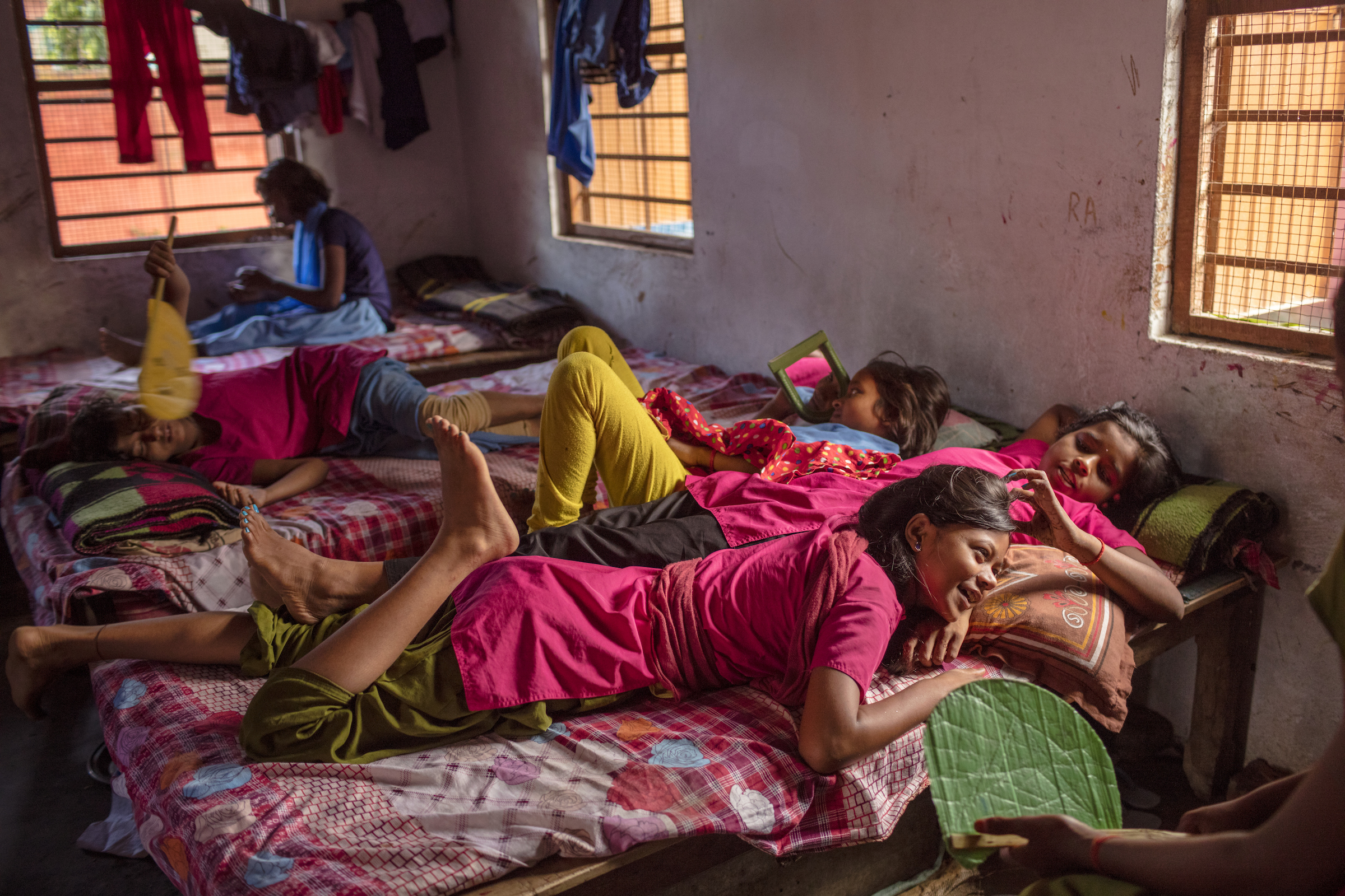 Rinki (foreground) and Arti relax beside each other in their room during a break between classes at their government-funded school, the Kasturba