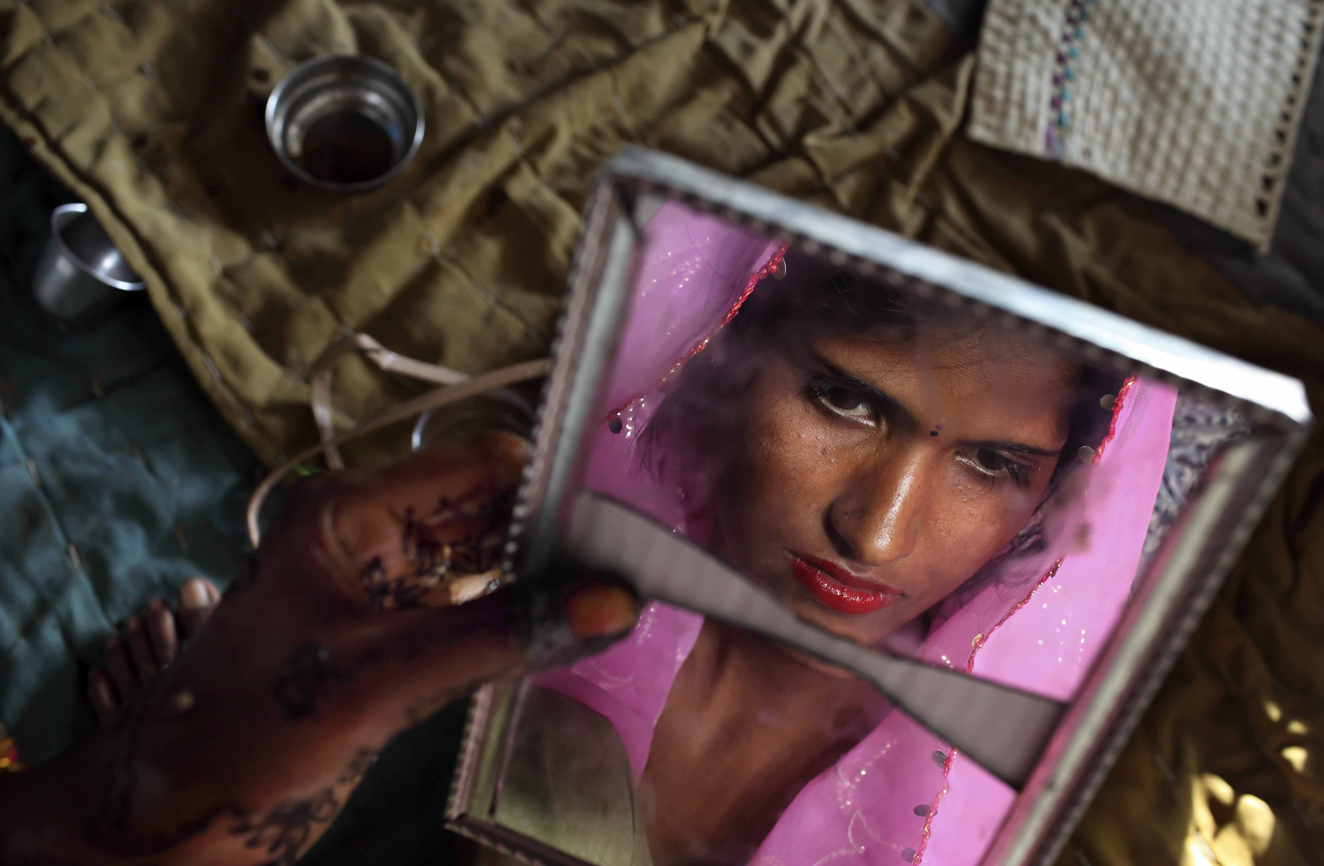 Radha, 15, observes herself in a cracked mirror the day before her wedding. Three young sisters Radha and her two younger sisters were married to three young sibling grooms on the Hindu holy day of Akshaya Tritiya in North India.